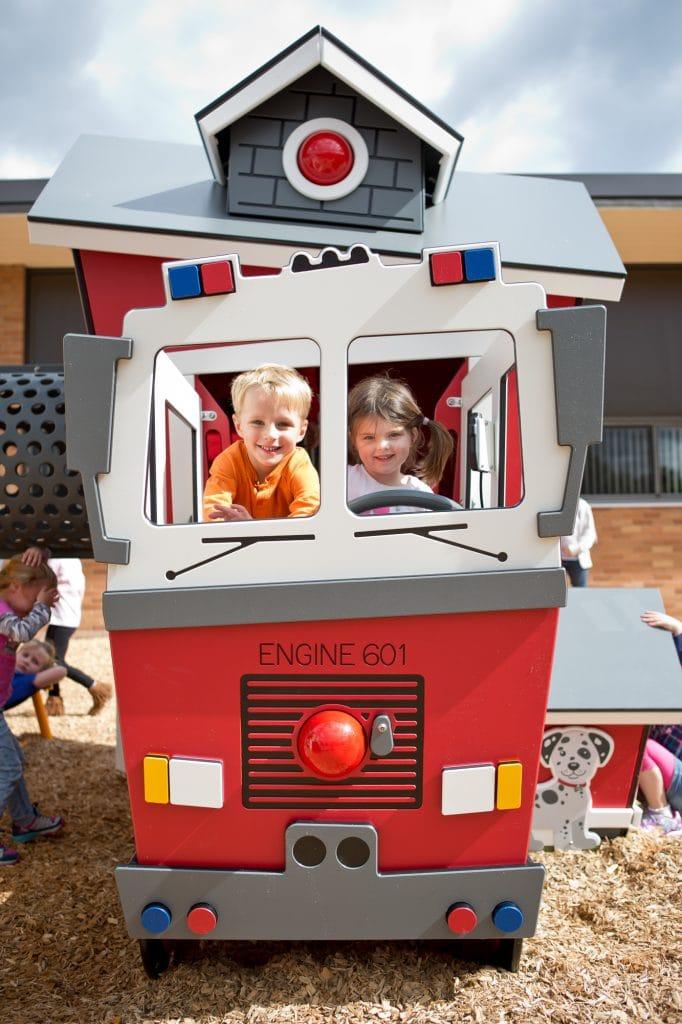 Kids playing on mini firetruck image